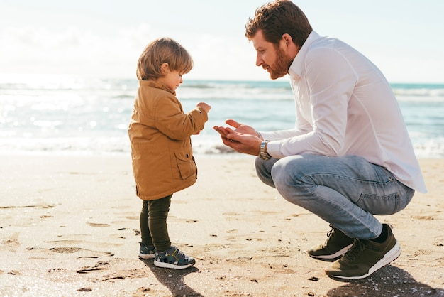 Adorable toddler getting familiar with beach sand Free Photo