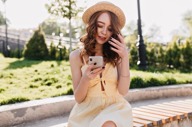 Прелестная белая девушка с черным маникюром расслабляет в красивом летнем парке. на открытом воздухе фото изящной рыжеволосой модели на смартфоне во время фотосессии. Бесплатные Фотографии