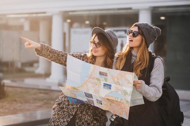 Donna adorabile in cappello lavorato a maglia grigio che cammina con l'amico intorno alla città e che tiene mappa. outdoor ritratto di due affascinanti viaggiatori femminili guardando qualcosa inetersting in lontananza e puntare il dito. Foto Gratuite