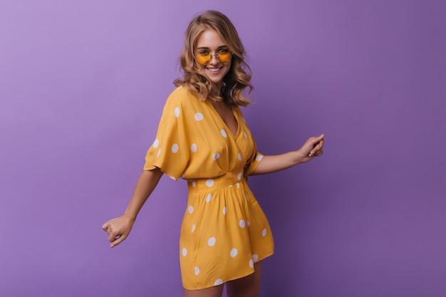 カメラに笑っているヴィンテージオレンジ色の服装の愛らしい女性。紫色に分離された波状のブロンドの女の子と壮大な女の子の肖像画。 無料写真