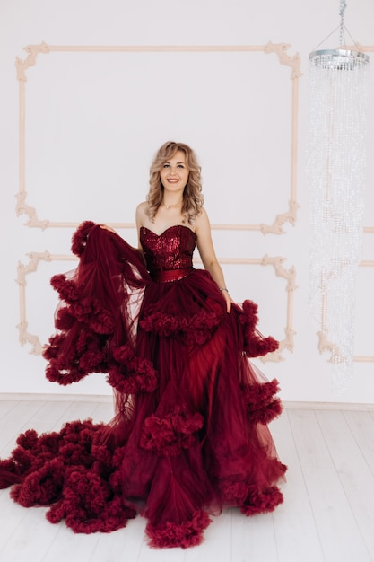 Adorable woman in red burgundi dress poses in a bright luxury room with large chandelier Free Photo