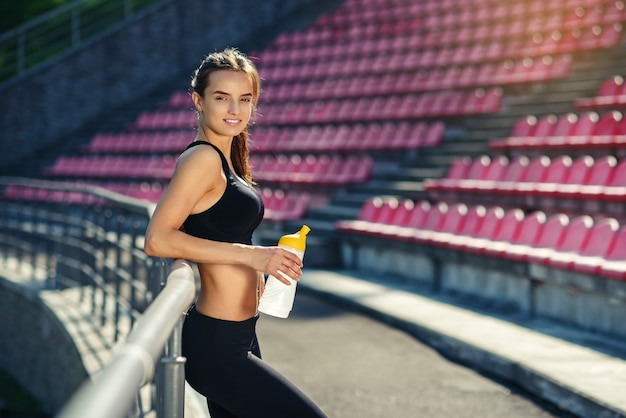 Adorable woman on the stadium tribune after training with the bottle of water in her hand Premium Photo