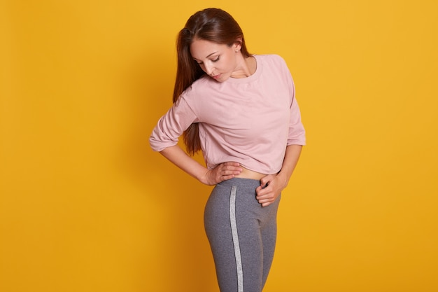 Adorable woman with perfect body in sport wear isolated on yellow, sporty female looking at result of her hard work, lady with pumped buttocks. sport and fitness concept Free Photo