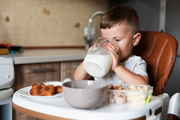 Adorable young boy drinking milk Free Photo