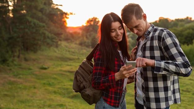 Adorable young couple browsing mobile phone Premium Photo