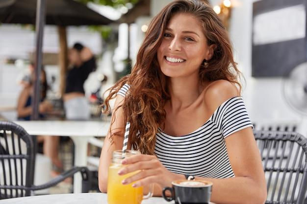 Adorabile giovane femmina con i capelli lunghi scuri, vestita con una maglietta a righe in una caffetteria, beve succo di frutta fresco e caffè espresso. Foto Gratuite