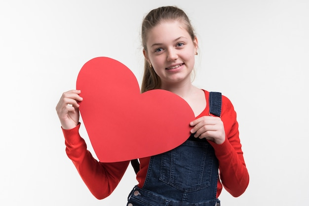 Adorable young girl holding a heart Free Photo