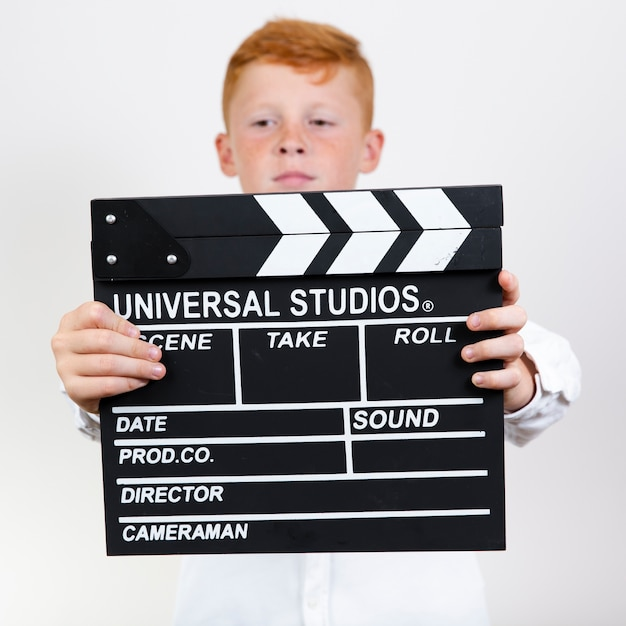 Adorable young kid holding clapperboard Free Photo