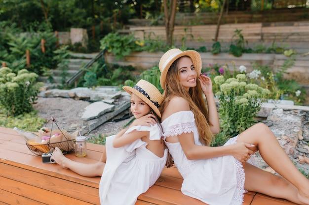 石と花のある美しい公園で楽しんでいる気分の良い愛らしい若い女性。トレンディなカンカン帽の母親の近くに座っているオープンバックのドレスを着た少女の屋外の肖像画。 無料写真