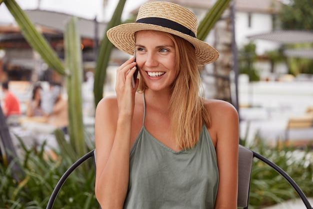 陽気な表情の愛らしい若い女性、さりげなく服を着て、電話での会話、夏の帽子を着て、屋外の椅子に座って、素晴らしいビーチを散歩した後に感銘を受けた 無料写真