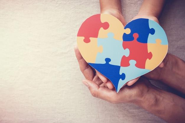 Руки взрослого и ребенка, держа головоломки сердце, концепция психического здоровья, всемирный день осознания аутизма Premium Фотографии