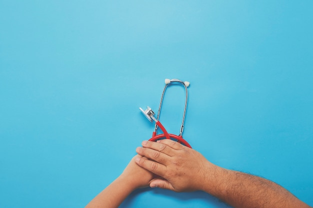 赤い聴診器を保持している大人と子供の手 Premium写真