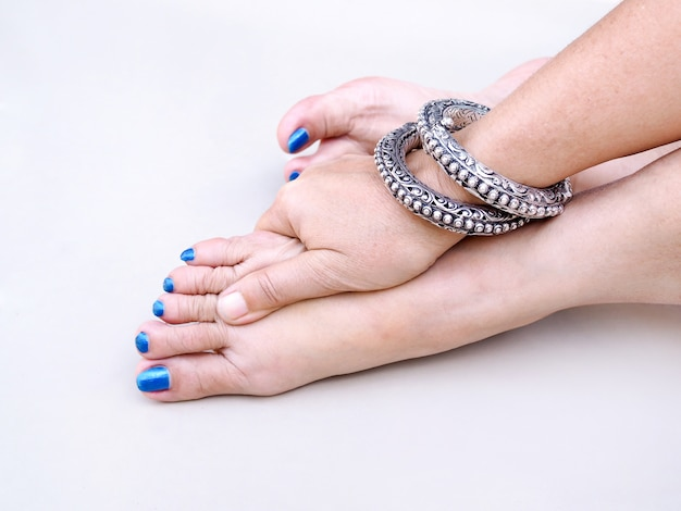 Adult asian woman with blue toenails and wear profit on wrist, use hand massage on feet to relax. Premium Photo