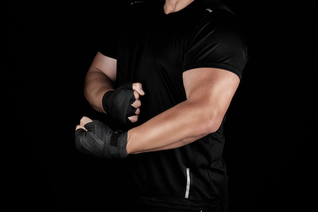 Adult athlete in black uniform is standing in a rack with strained muscles Premium Photo