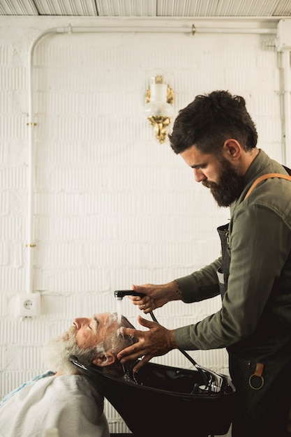 Adult barber washing old man hair on backwash Free Photo