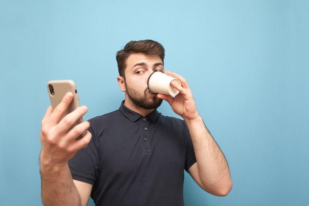 Взрослый бородатый мужчина пьет кофе из бумажного стаканчика и использует смартфон на синем Premium Фотографии