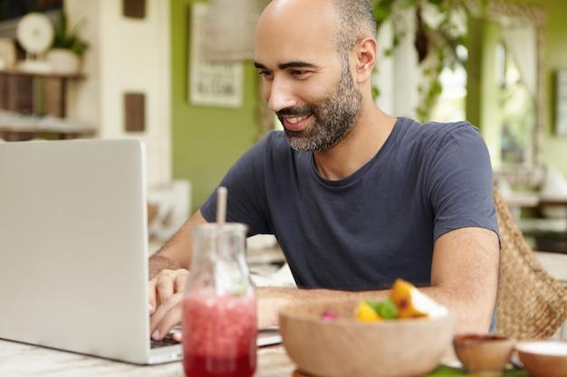 大人のひげを生やした男がカフェで朝食をとり、汎用のラップトップの前のテーブルに座って、ソーシャルネットワーク経由で友達にメッセージを送りながら笑顔で見て、無料のwi-fiを楽しんでいます。 無料写真