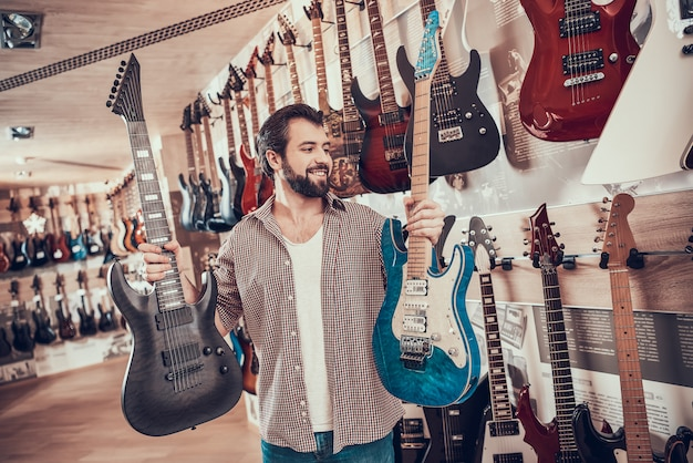 Adult bearded man makes choice between two electric guitars. Premium Photo