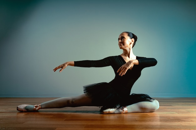 45〜55歳の大人の美しい女性、トウシューズのバレリーナが床に座ってカメラにポーズ Premium写真