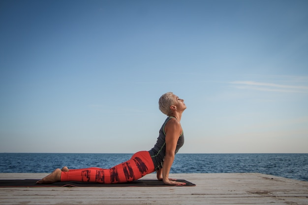Adult blond woman with short haircut practices yoga on the pier against the background of the sea and blue sky Premium Photo