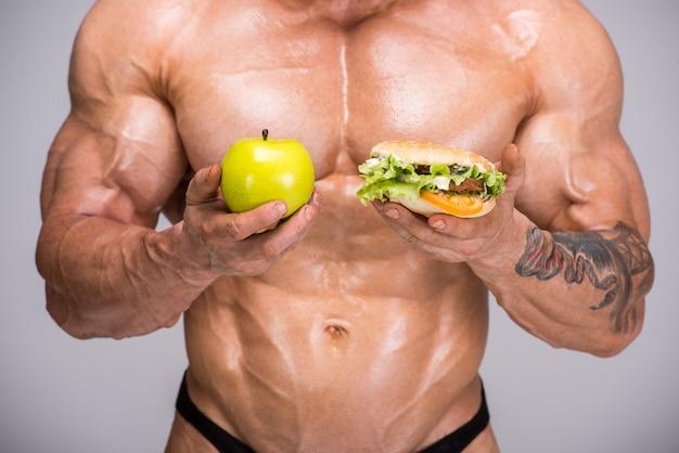 Adult bodybuilder is holding apple in his hand. Premium Photo