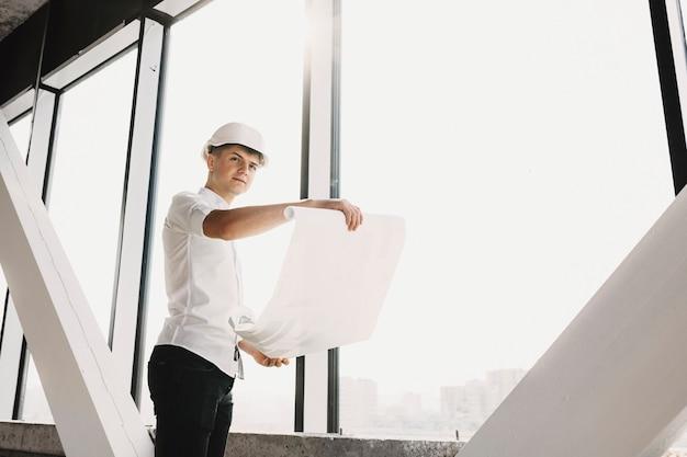 성인 사업가 큰 창 근처 건설에서 건물의 계획을 잡고 멀리 웃 고 찾고 보호 헬멧을 갖추고 있습니다. 프리미엄 사진