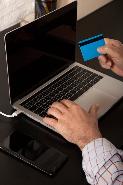 Adult businessman using a credit card and using laptop making an online purchase from home. online shopping Premium Photo