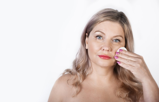 Взрослая кавказская блондинка чистит лицо ватным диском, позирует с обнаженными плечами на белой стене Premium Фотографии