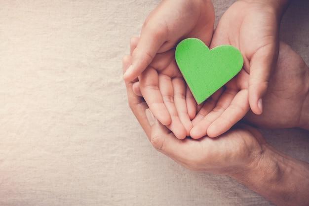 Adult and child hands holding green heart, vegan vegetarian, sustainable living, healthy wellness, csr social responsibility concept, world environment da, world health day Premium Photo