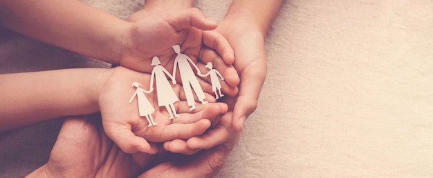 Adult and children hands holding paper family cutout, family home, foster care, homeless support Pre