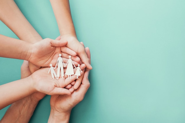Adult and children hands holding paper family cutout Premium Photo