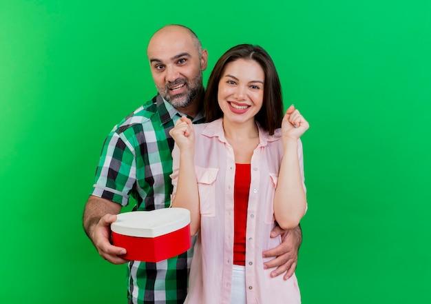 大人のカップルは、拳を握り締める女性の笑顔の女性の腰に手を置くハート型の箱を持っている男性に感銘を与えました 無料写真