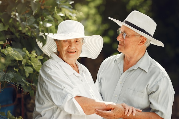 Adult couple in a summer garden. handsome senior in a white shirt. woman in a hat. Free Photo