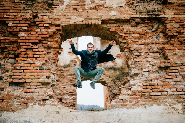 Adult crazy angry unusual excited male portrait. businessman in flight motion. young boy with funny comic expressive odd face emotions jumping from brick wall. flying person. sport activity outdoor Premium Photo