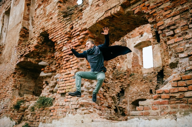 Adult crazy angry unusual excited male portrait. businessman in flight motion. young boy with funny comic expressive odd face emotions jumping from brick wall. Premium Photo