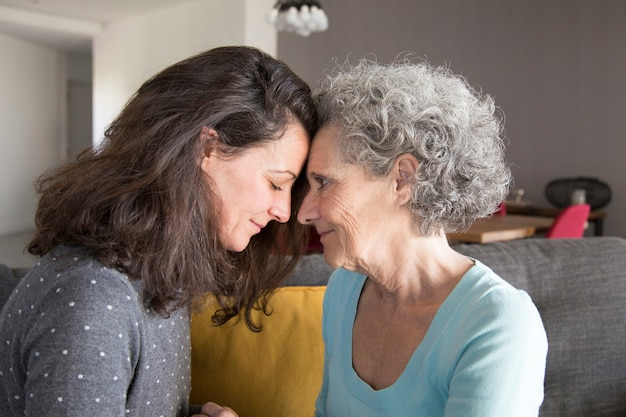 Adult daughter and old mother touching foreheads Free Photo