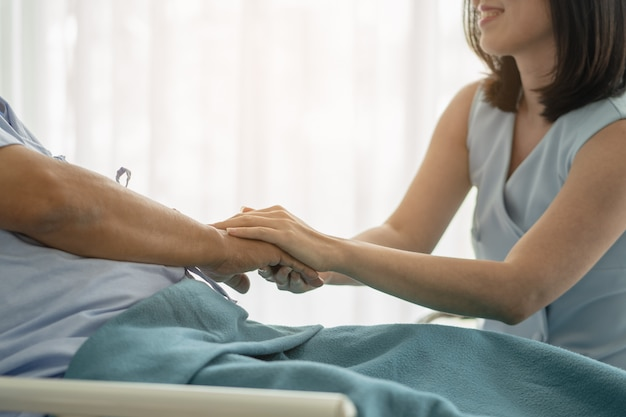 Adult daughter touching hands of her father and encouraging to fight cancer in hospital Premium Photo