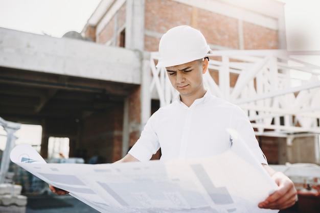 성인 유럽 남성 마스터 건설에있는 건물의 계획을 심각 하 게보고. 프리미엄 사진