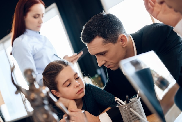 Adult father calms daughter while sitting at desk in office Premium Photo