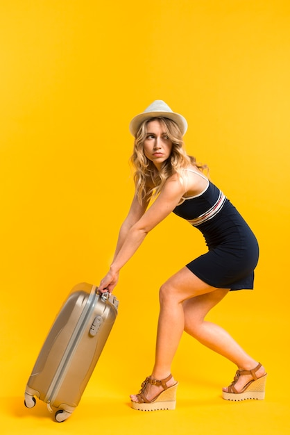 Adult female in summer outfit carrying heavy luggage Free Photo