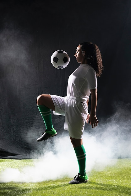 Adult fit woman playing with football Free Photo
