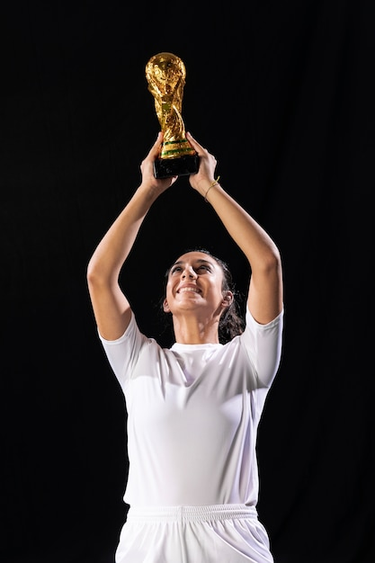 Adult fit woman raising soccer trophy Free Photo