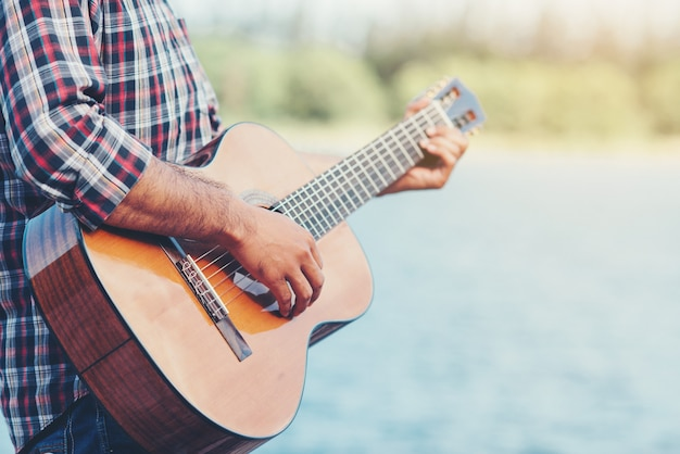 Adult handsome musician playing acoustic guitar Free Photo