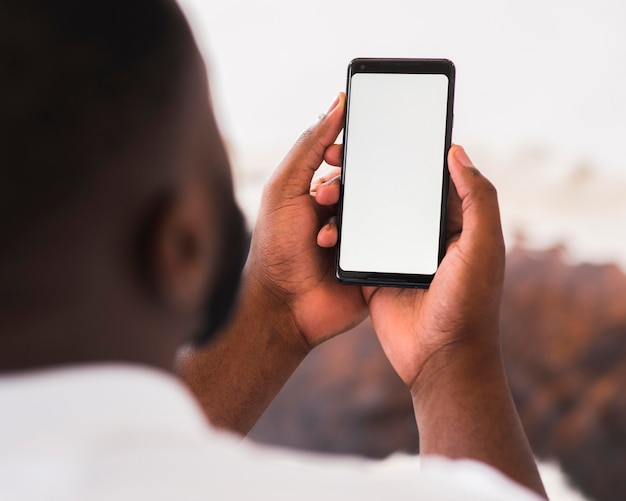 Взрослый мужчина держит мобильный телефон Premium Фотографии
