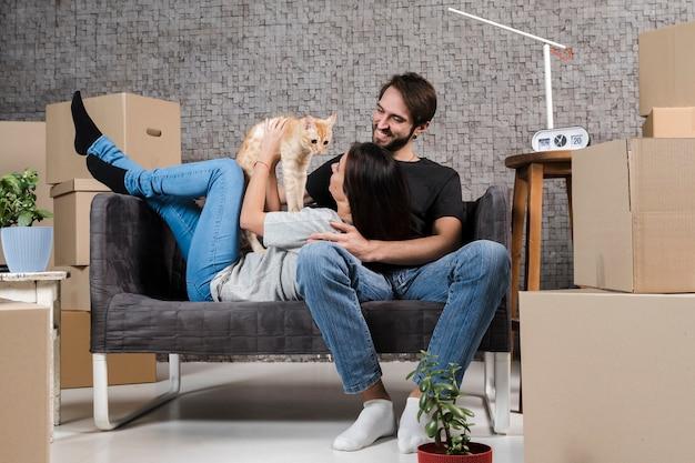 Взрослый мужчина и женщина в помещении с семейной кошкой Premium Фотографии