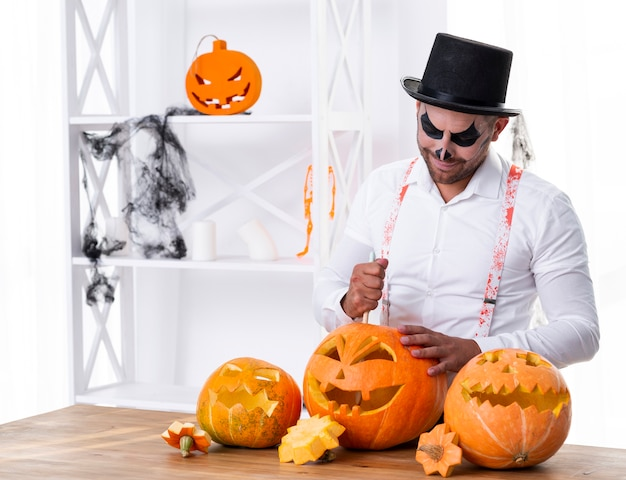 Adult man carving pumpkins for halloween Free Photo