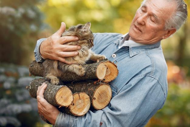 Взрослый мужчина держит дрова и кота Бесплатные Фотографии