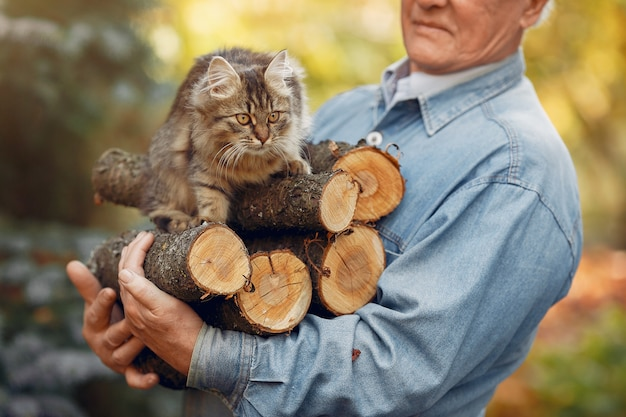 Adult man holding firewood and a cat Free Photo