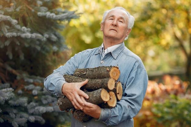 Adult man holding firewood outside Free Photo