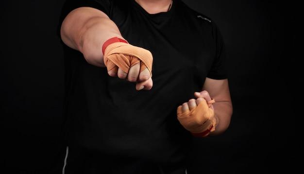 Взрослый мужчина в черной форме и мускулистые руки стоит в спортивной позиции Premium Фотографии